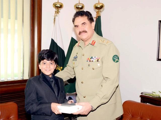 راولپنڈی:آرمی چیف جنرل راحیل شریف اولیول عالمی ریکارڈیافتہ بچے رائے حارث منظورکوتحفہ دے رہے ہیں۔ فوٹو: پی پی آئی