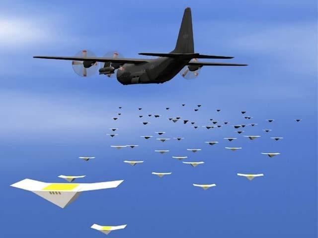 ایک مصورانہ خاکے میں درجنوں چھوٹے ڈرونز ایک بڑے ہوائی جہاز سے باہر پرواز کرتے دیکھے جاسکتے ہیں۔ فوٹو: بشکریہ امریکن نیول ریسرچ