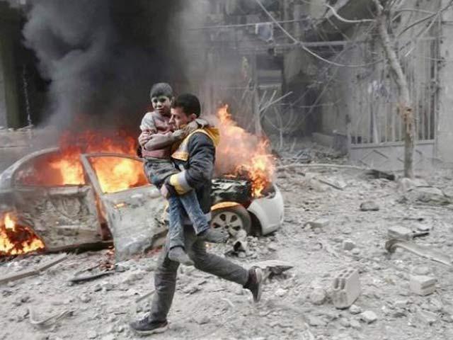 شام کے علاقے مشرقی غوطہ میں بمباری کے بعد ایک شخص بچے کو دوڑتے ہوئے محفوظ مقام تک پہنچارہا ہے۔ فوٹو: بشکریہ سی این این