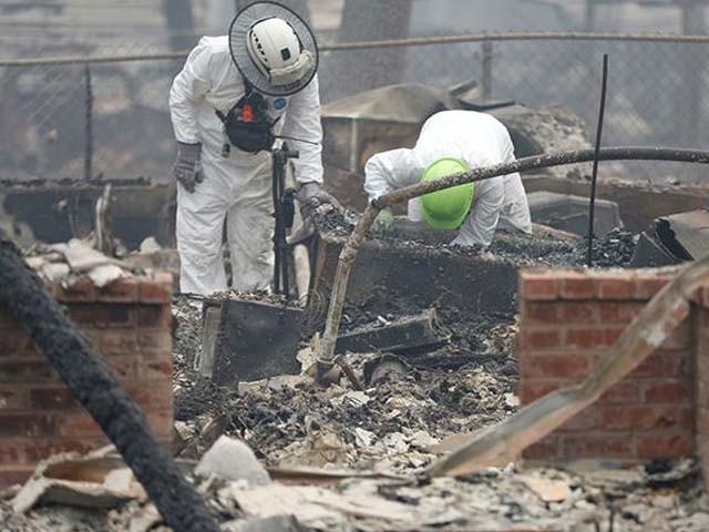 ریسکیو ادارے کے اہلکار راکھ کے ڈھیر کو ہٹانے کے کام میں مصروف ہیں۔ فوٹو : رائٹرز