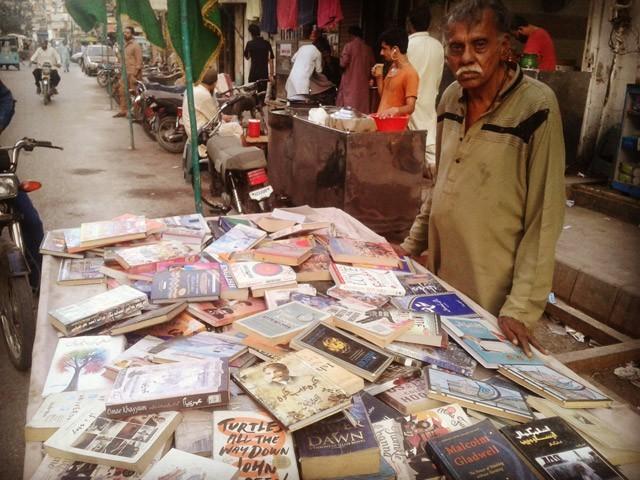 پچپن سالہ حنیف چاچا، جو پچھلے کئی سال سے سول اسپتال کے قریب پرانی کتابیں فروخت کرتے ہیں۔ (تصویر: بلاگر)