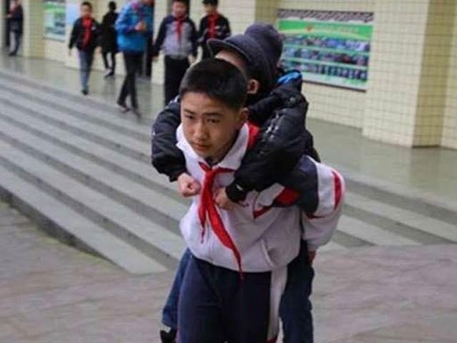 چین میں 12 سالہ بچہ اپنے دوست کو روزانہ پیٹھ پر سوار کرکے اسے گھر سے اسکول اور اسکول سے گھر تک لاتا ہے (فوٹو: اوڈٹی سینٹرل)
