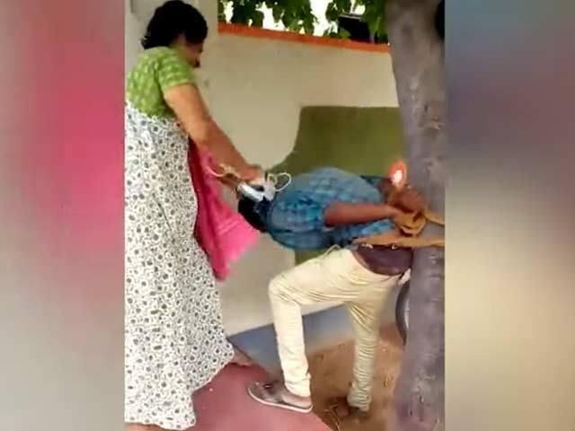 خاتون کے شوہر نے لڑکے کو درخت سے باندھا اور خاتون نے دل بھر کے پٹائی کی۔ فوٹو : ویڈیو گریب