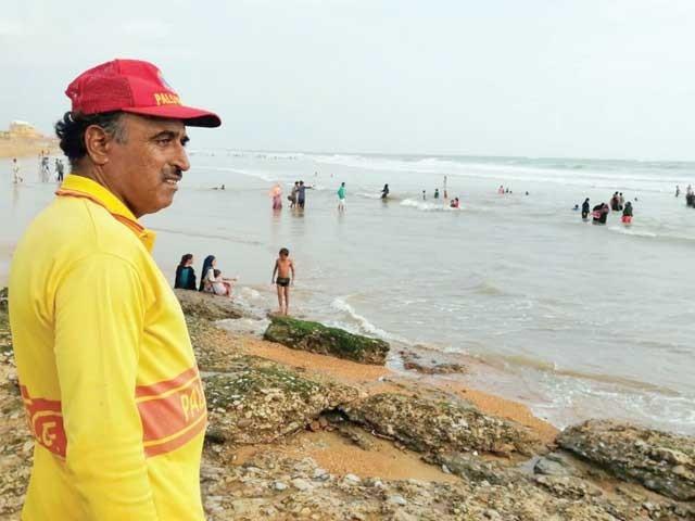 ہاکس بے کے ساحل پر لائف گارڈ محمد انور فرائض کی ادائیگی کے دوران شہریوں پر نظر رکھے ہوئے ہے ۔  فوٹو : ایکسپریس
