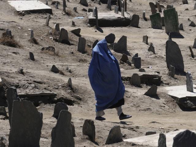 افغان خاتون ایک قبرستان سے گزر رہی ہیں۔ فوٹو : فائل