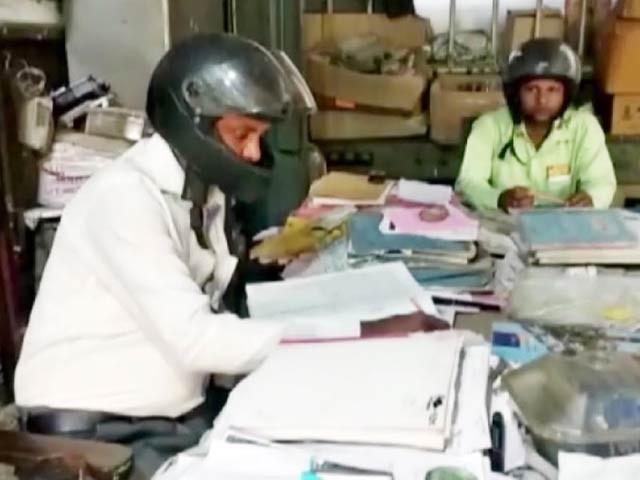 بھارت میں سرکاری دفتر کے اہلکار بوسیدہ عمارت سے گرنے والے پتھر اور پلستر سے بچنے کے لیے دورانِ کار ہیلمٹ پہننے پر مجبور ہیں۔ فوٹو: اے این آئی