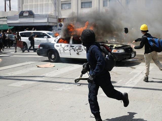 پولیس موبائلز سمیت کئی گاڑیاں نذرآتش، متعدد دکانوں کو لوٹ لیا گیا فوٹو: اے ایف پی