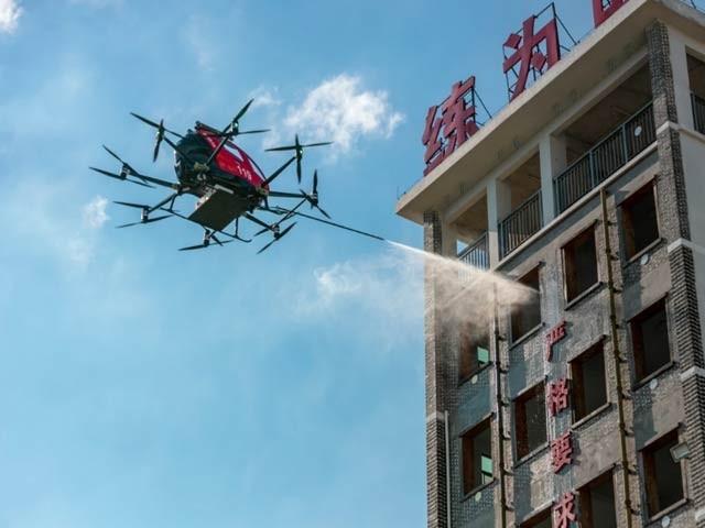 تصویر میں ای ہینگ ڈرون تجرباتی طور پر ایک عمارت میں آگ بجھانے میں مصروف ہے۔ فوٹو: ای ہینگ