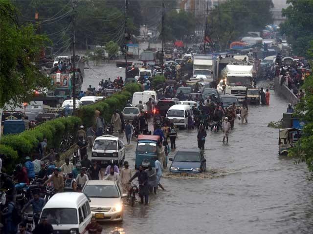 جمعرات کی بارش کے دوران لوگوں کے پانی میں پھنس جانے اور ٹریفک جام کا منظر (فوٹو : اے ایف پی)
