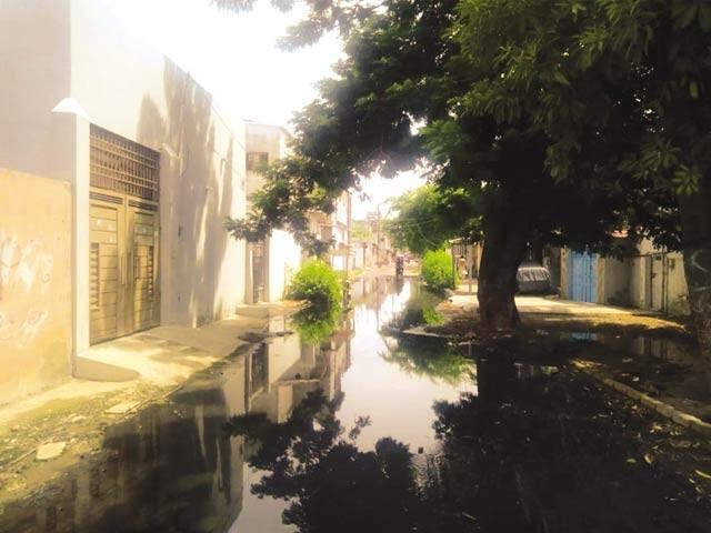 کلنٹن کوارٹرز کی گلیوں میں سیوریج کا پانی جمع ہے دوسری تصویر میں سڑک تباہی سے دوچارنظر آرہی ہے  ۔  فوٹو : ایکسپریس