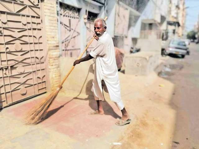وارث سندر گلی کی صفائی کے بعد کچرا ٹرالی میں ڈال کر لے جارہا ہے