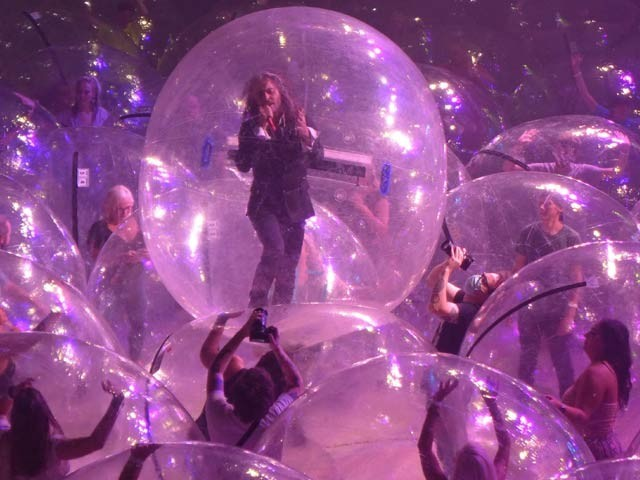 امریکہ کا میوزیکل بینڈ 'فلیمنگ لِپس' تمام شرکا کو کوڈ پلاسٹک کے بلبلوں میں بند کنسرٹ میں ہے۔  فوٹو: سی این