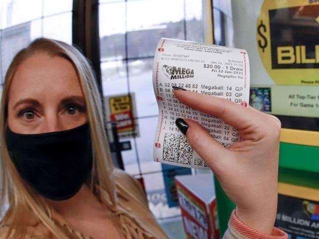 تصویر میں اپنا نام نہ بتانے والی خاتون ایک ارب ڈالر ٹکٹ کے ساتھ اسموکر فرینڈلی اسٹور میں موجود ہیں جہاں سے انہوں نے ٹکٹ خریدا تھا۔ تصویر اے پی