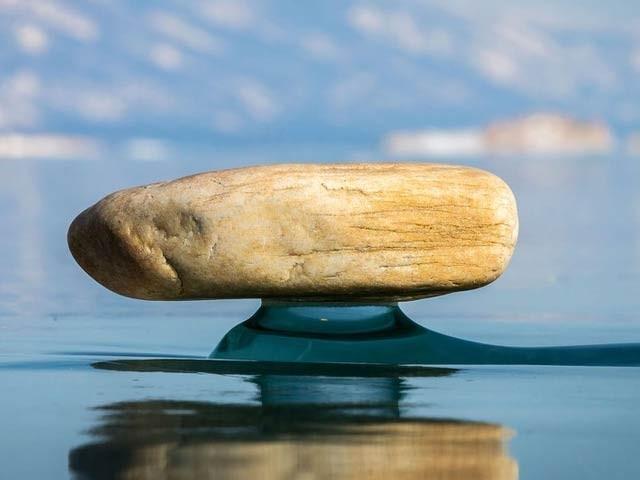 تصویر زین بیکل نامی مظہر دیکھا جاسکتا ہے جس میں منجمند پانی پر رکھا ایک پتھر نمایاں ہے۔ فوٹو: اٹلانٹس میگزین