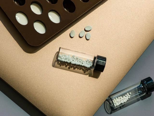 تصویر میں شیشے سے باہر کی بڑی گولیوں کو نئے طریقے سے چھوٹا کرکے بنایا گیا ہے جسے شیشی کے اندر دیکھا جاسکتا ہے۔ فوٹو: ایم آئی ٹی