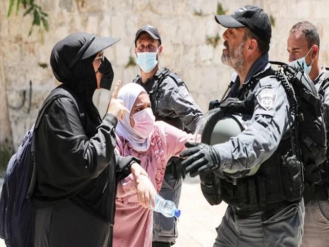 اسرائیلی فوجی خواتین کو زبردستی مسجد اقصیٰ سے نکال رہا ہے، فوٹو: رائٹرز