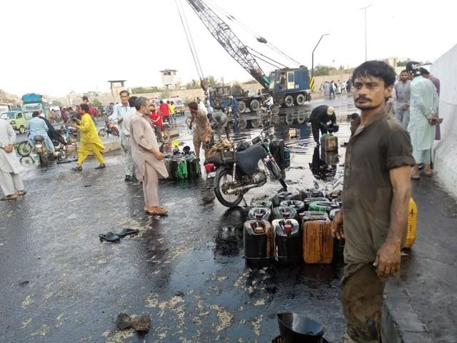 علاقہ مکینوں نے سڑک پر بہہ جانے والے تیل کو پلاسٹک کے کینز میں بھر لیا تاہم پولیس کی جانب سے شہریوں کونہیں روکا گیا۔(فوٹو: ایکسپریس)