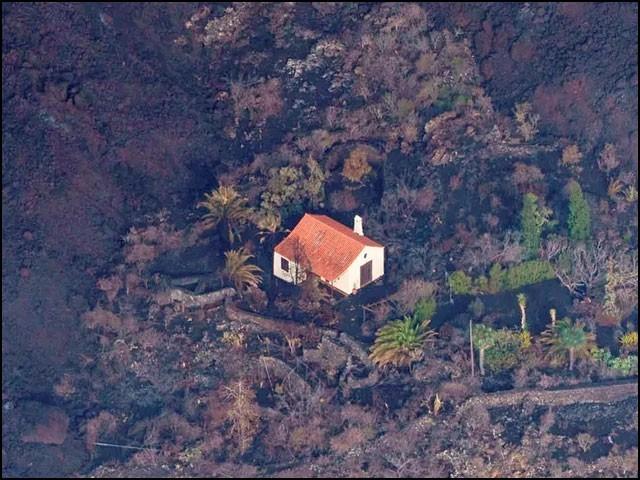 گرم آتش فشانی لاوے نے پورے جزیرے کو گھیر لیا ہے لیکن یہ مکان معجزاتی طور پر بالکل محفوظ ہے۔ (فوٹو: ایل موندو/ ہسپانوی ویب سائٹ)